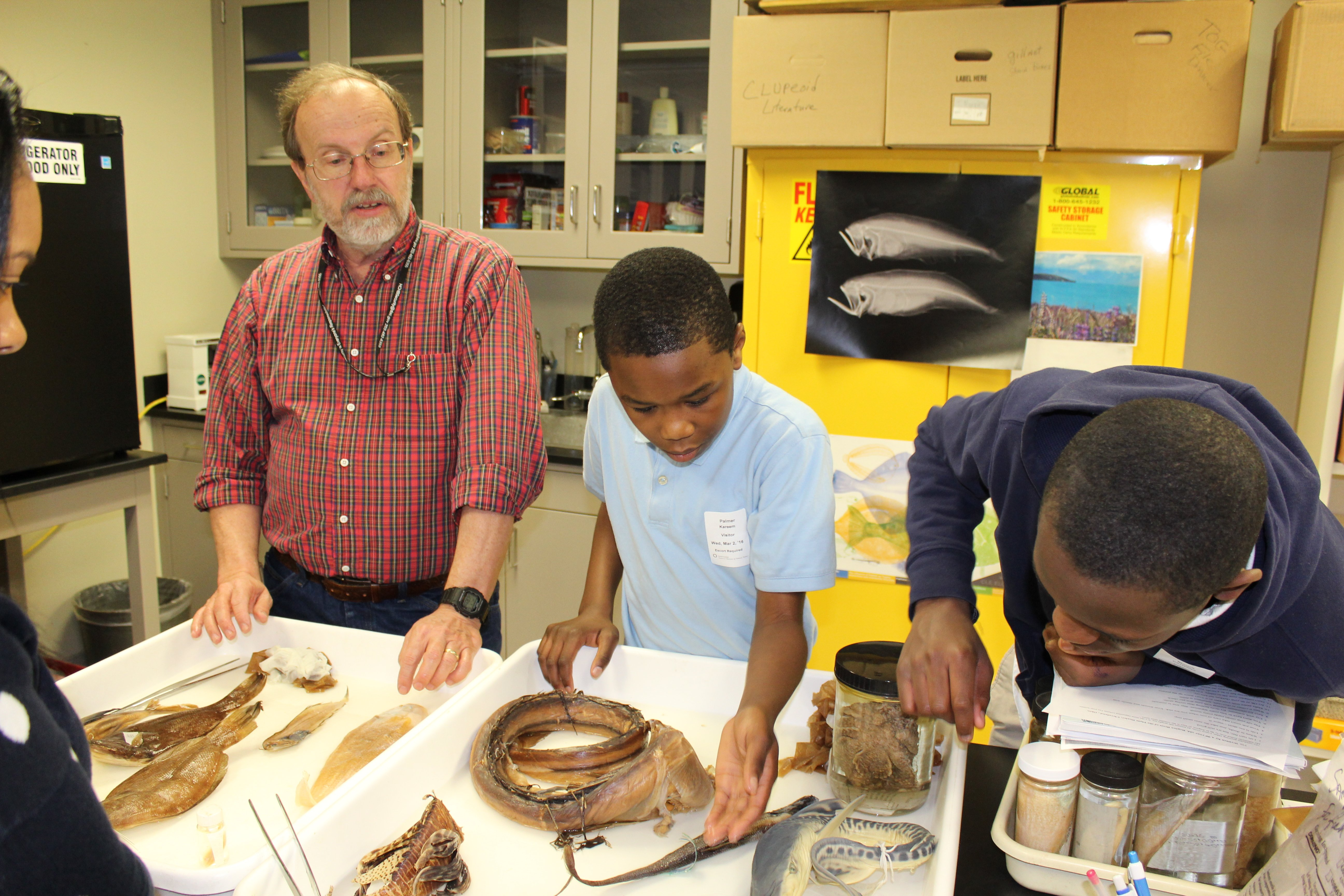 Students examine deep sea fishes with NOAA scientist Dr. Tom Munroe