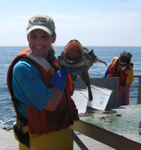 library media specialist holds a monkfish on a research vessel